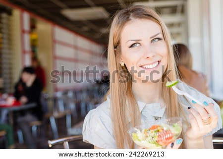cheerful young pretty lady sitting in restaurant holding a delicious salad and smiling at camera