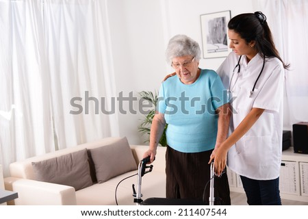 cheerful young rehab nurse helping elderly woman using a walker  - stock photo