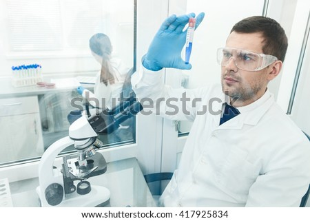 Cheerful young researchers are working in lab - stock photo