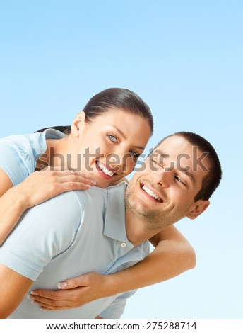 Cheerful young smiling amorous attractive couple, against blue sky background, with blank copyspace area for text or slogan - stock photo