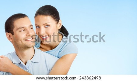 Cheerful young smiling amorous attractive couple, against blue sky background, with copy space for slogan or text - stock photo