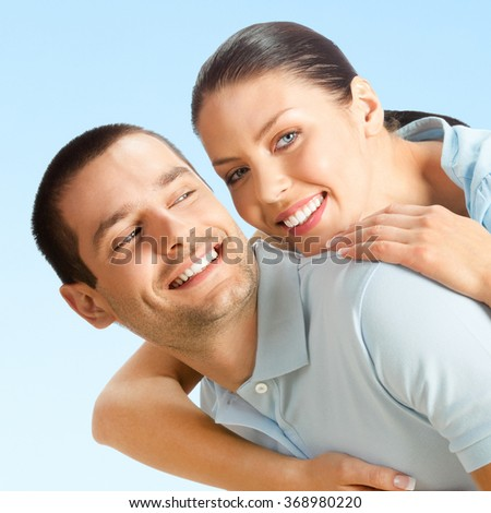 Cheerful young smiling amorous attractive couple, over blue sky background