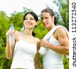 Cheerful young smiling couple on outdoor fitness workout - stock photo