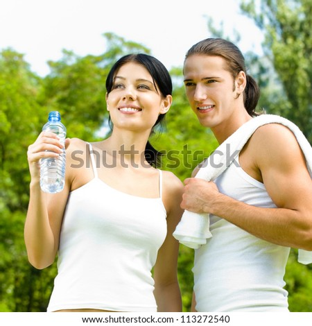 Cheerful young smiling couple on outdoor fitness workout