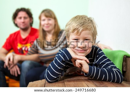 Cheerful young smiling son sitting on foreground of his parent on the sofa - stock photo