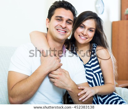 Cheerful young spouses posing and hugging in living room.Focus on the man - stock photo