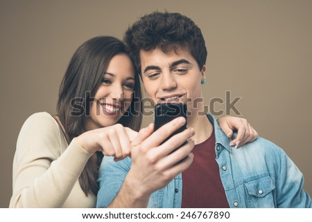 Cheerful young teen smiling couple with mobile phone enjoying together - stock photo