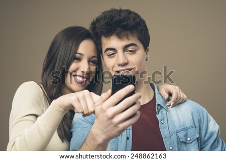 Cheerful young teen smiling couple with mobile phone enjoying together