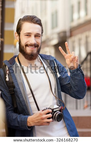 Cheerful young tourist is making photos in city. He is standing and holding camera. The hipster guy is showing peace sign and smiling. He is looking forward happily - stock photo