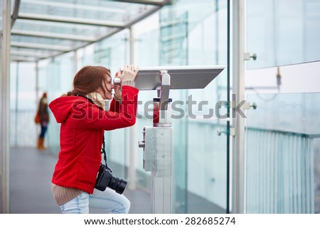 Cheerful young tourist using telescope on the Montparnasse tower observation deck in Paris - stock photo