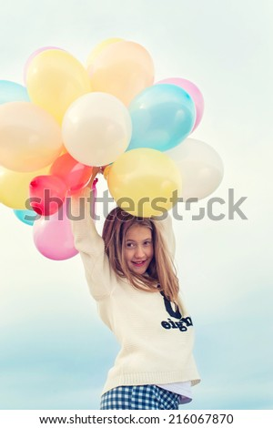 Cheerful young trendy girl with bunch colored balloons. Outdoors with instagram filter. - stock photo