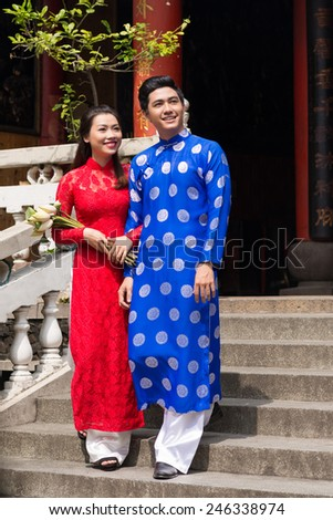 Cheerful young Vietnamese couple in ao dai dresses