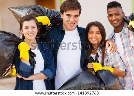 cheerful young volunteers with garbage bag after cleaning the streets - stock photo