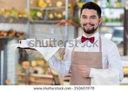 Cheerful young waiter is holding a tray with cups of tea. He is standing and smiling. The man is looking at camera happily - stock photo