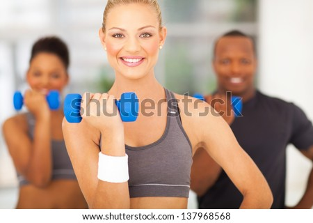 cheerful young woman and friends exercising with dumbbells - stock photo