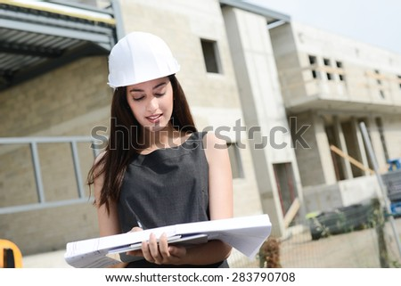 cheerful young woman architect supervising building construction site with a  blueprint