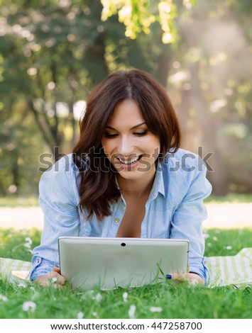 Cheerful, young woman browsing her tablet in the park.