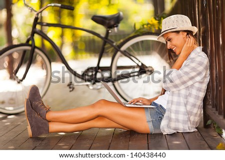cheerful young woman browsing internet on her laptop outdoors at the park - stock photo