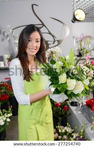 cheerful young woman brunette florist selling flowers in a flower shop - stock photo