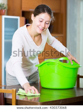 Cheerful young woman cleaning indoors with smile on face - stock photo