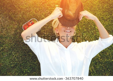 Cheerful young woman closes own eyes from the sunlight using stylish hat while enjoying summer vacation, hipster girl with beautiful smile hiding face under headgear while lying on the grass in park - stock photo