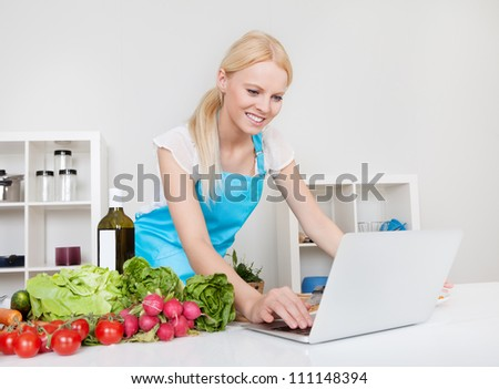 Cheerful young woman cooking in the kitchen