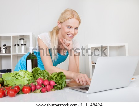 Cheerful young woman cooking in the kitchen - stock photo
