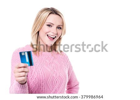 Cheerful young woman displaying credit card to camera - stock photo