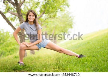 Cheerful young woman doing exercises in park - stock photo