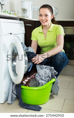 Cheerful young woman doing laundry at home  - stock photo