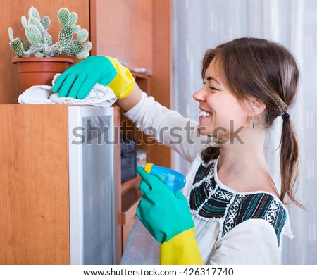 Cheerful young woman doing regular clean-up indoors - stock photo