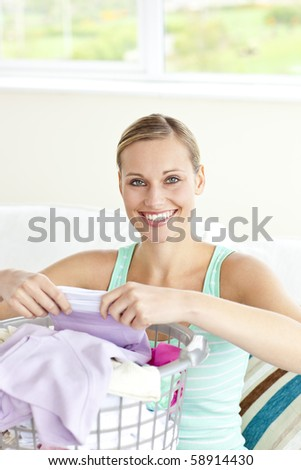 Cheerful young woman doing the laundry at home - stock photo