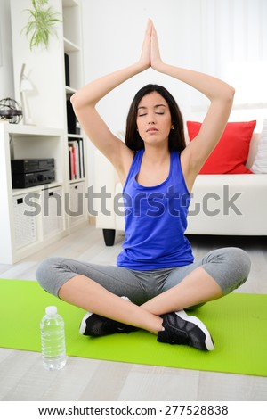 cheerful young woman doing yoga relaxation exercises at home - stock photo