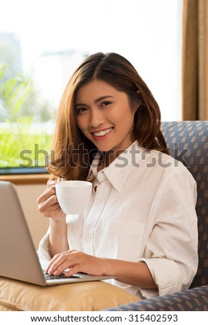 Cheerful young woman drinking morning coffee and checking e-mail