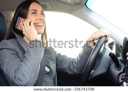 cheerful young woman driving a car and talking on the smartphone - stock photo