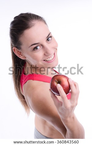 cheerful young woman eating a red apple - stock photo