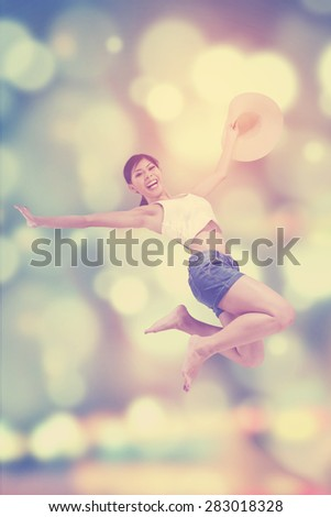Cheerful young woman enjoy freedom and feel free by jumping over blur background - stock photo