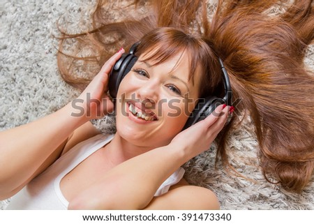 Cheerful young woman enjoying music in headphones.