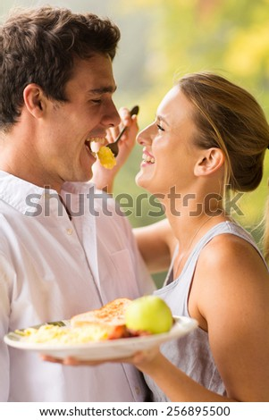 cheerful young woman feeding boyfriend breakfast - stock photo