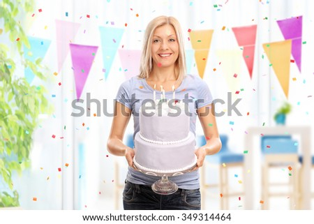 Cheerful young woman holding a birthday cake and looking at the camera at homed - stock photo