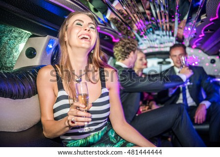 Cheerful Young Woman Holding Champagne Flute In Limo
