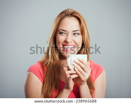 Cheerful young woman holding cup of tea or coffee. Studio Shot - stock photo