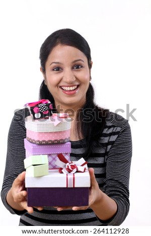 Cheerful young woman holding many gift boxes