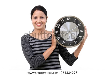 Cheerful young woman holding office clock - stock photo