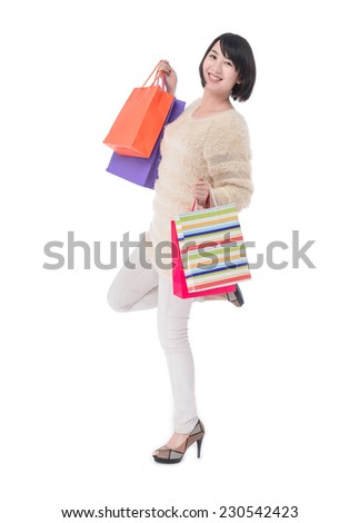 Cheerful young woman holding shopping bags posing