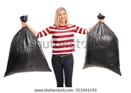Cheerful young woman holding two black trash bags and looking at the camera isolated on white background