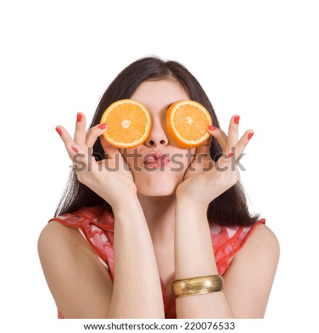 Cheerful young woman holding two halves of orange in front of her eyes