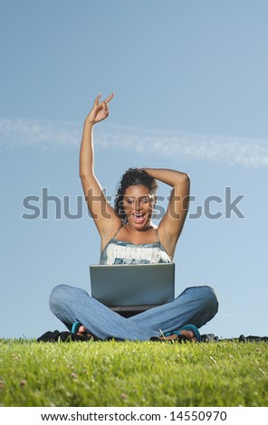 Cheerful young woman in a meadow working online - stock photo