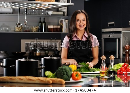 Cheerful young woman in apron on modern kitchen cutting vegetables - stock photo