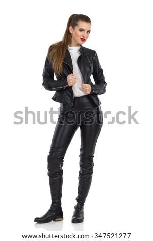 Cheerful young woman in black leather trousers, jacket and boots standing looking at camera. Full length studio shot isolated on white.